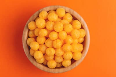 Cheese puff balls in wooden bowl on bright colorful background
