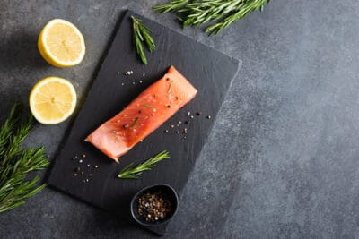 Fresh raw salmon red fish fillet with spices, herbs and lemon