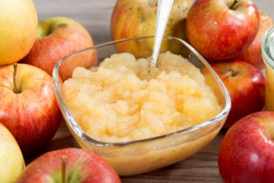 A bowl of applesauce with apples on a wooden table.