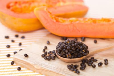 seed of yellow papaya on spoon and wood block with yellow papaya on behind